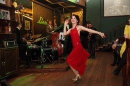 Picture of Ksenia Parkhatskaya swing dancing in a red dress in a blog about Dance Shoes