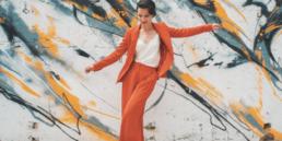 Photo of Ksenia swing dancing in a orange suit wall