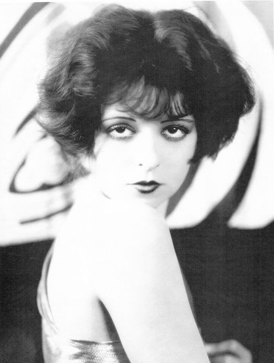 Clara Bow, one of the 3 most famous flappers, represents perfect flapper face and figure. Big - eyed, baby - faced flapper image.